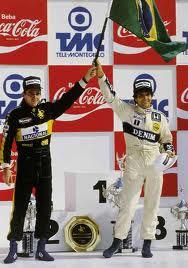 Senna and Piquet at a podium holding together a Brazilian flag