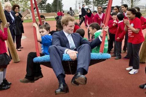 Prince Harry sitting in a big swing with school children