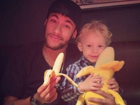 neymar eating a banana and carrying his son