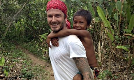 Beckham carrying pig back an yanomani boy